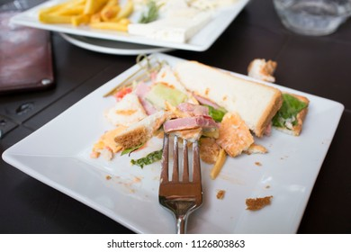 fork on a plate with half-eaten food in the cafe on the table