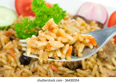 Fork with pilaf and vegetables.