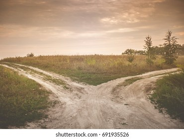 Fork in the road. A country road splits in two, making a decision-requiring fork in the road. Concept image