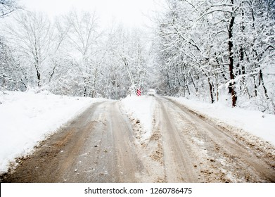 Fork in the road. A winter country road splits in two, making a decision-requiring fork in the road. Concept image