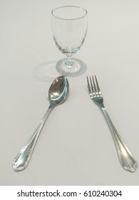 fork and spoon and glass on white table