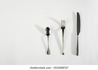 fork spoon and knife on a white background with hard shadows from the sun's rays. top view close-up. cutlery. Subject photography.