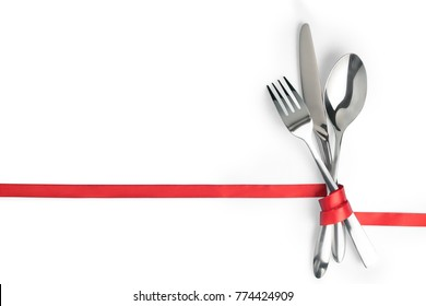 Fork, spoon and knife tied with a red ribbon. Isolated on white, clipping path included. Food, restaurant and table setting theme template with copy space