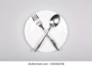 Fork and spoon on an empty white plate on gray background.  intermittent fasting, diet, biohacking weight loss concept.