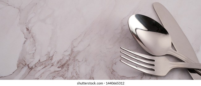 Fork and spoon on marble texture background, banner concept