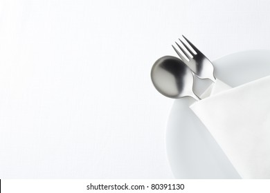 Fork and spoon on white plate.