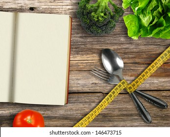 Fork and spoon tied with tape measure with book and vegetables on wooden background (diet concept)