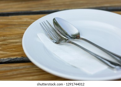 fork and spoon with white plate on wood table