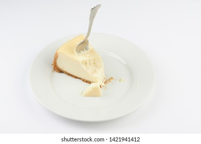 Fork stuck in cheesecake with bite on plate isolated
