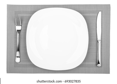 Fork, table knife and empty white plate on a placemat closeup, top view