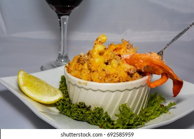 A fork taking a bite of the Lobster Macaroni and Cheese served with a glass of red wine