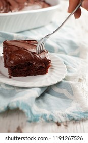 Fork taking a bite out of Dark Chocolate Buttercream Frosting on a moist and delicious chocolate cake