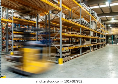 A forklift captured in motion driving through a warehouse between the racks