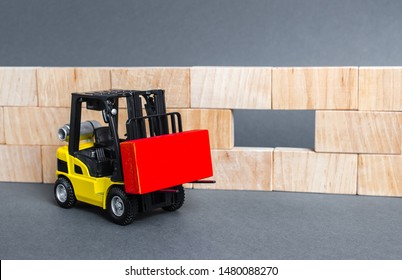 A forklift carries a red block to insert into a wall void. A key element to complete the project, part of the whole. Innovation, concept of idea. Cooperation and collaboration. Teamwork