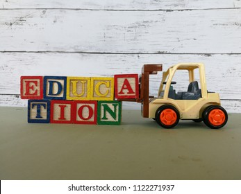 Forklift carry wooden block to complete the word Education.
