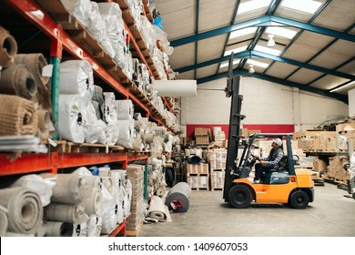 Forklift driver carefully transporting stock from shelves while working on the floor of a large carpet warehouse