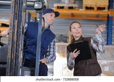 forklift driver and female supervisor with clipboard