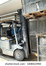 Forklift is handing bulk container be filled with white sludge.
