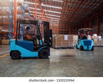 Forklift is handling cargo on pallet  in large warehouse.