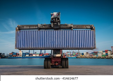 Forklift handling container box loading at port cargo at sunset