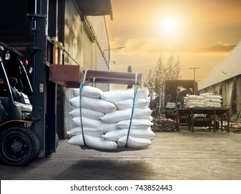 Forklift handling sugar bags outside from warehouse for stuffing into container for export.