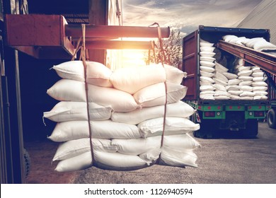 Forklift handling white sugar bags from warehouse for stuffing into container for export, vintage color.