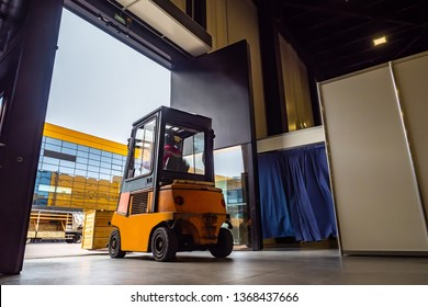 Forklift leaves the warehouse with a load. Forklift stock. Loader carries cargo. Gate warehouse. Unloading goods. Warehousing. Warehouse storage. Logistics in stock