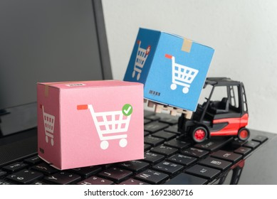 Forklift lift parcel carton box with shopping trolley cart logo on laptop computer with white wall background. E-commerce or online shopping, logistic inventory control, cash on delivery (COD) concept