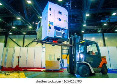 The forklift lifts the equipment. Transportation of industrial equipment. Unloading equipment. The loader unloads the machines in the production.