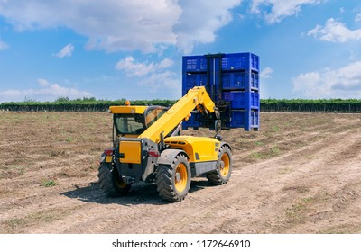 Forklift loader loads plastic containers.