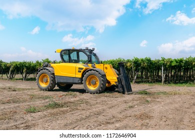 Forklift loader of yellow color in a field on a vineyard background.