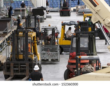 Forklift loaders and workers build stage