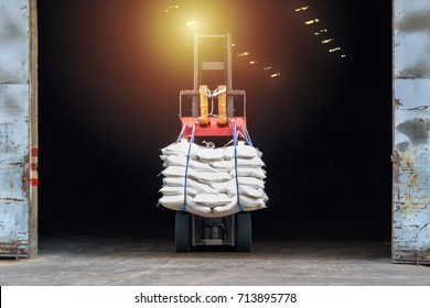 Forklift moving white sugar bags out of warehouse for stuffing into a container for export