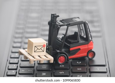 Forklift with new email graphic on wooden block over laptop keyboard. 2d illustration