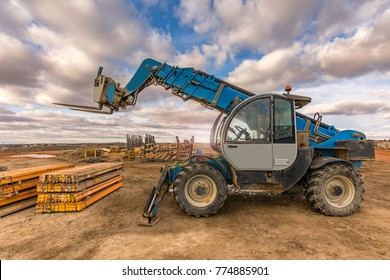 Forklift on a construction site, preparing to raise construction parts