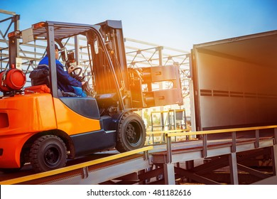 Forklift is putting cargo from warehouse to truck outdoors at sunny sky background.