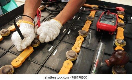 Forklift service ,fitting a Car service ,fitting a car battery with wrench.Uses a multimeter voltmeter to check the voltage level in a car battery