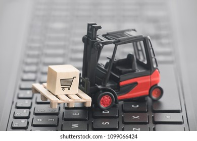 Forklift with shopping cart graphic on wooden block over laptop keyboard. 2d illustration