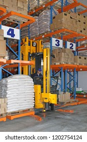 Forklift Stacker Between Aisles in Distribution Center Warehouse