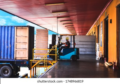 Forklift stuffing-unstuffing pallets of cargo to container on warehouse leveler dock. - Shutterstock ID 1748966819