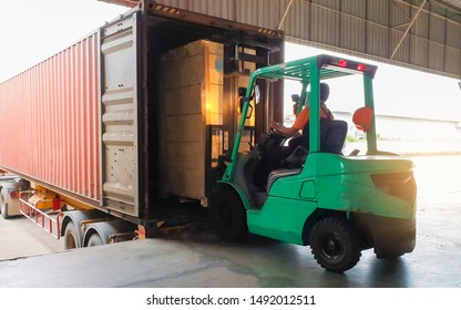 Forklift Tractor loading package boxes into shipping container at dock warehouse. Cargo shipment with truck. Supply Chain Freight truck. Industry warehouse logistics transportation.