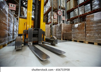 Forklift truck in aisle between storage shelves