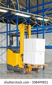 Forklift Truck with Boxes at Pallet in Warehouse