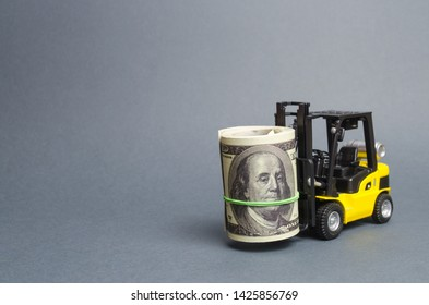Forklift truck carries a bundle of dollars. Attracting direct investment in business and production, improving economic performance. Export of capital, offshore economic zones. Capital and capitalism.