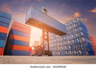 Forklift truck lifting cargo container in shipping yard or dock yard against sunrise sky for transportation import,export and logistic industrial concept.