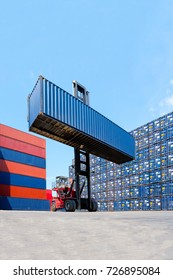 Forklift truck lifting cargo container in shipping yard or dock yard with cargo container stack in background for transportation import,export and logistic industrial concept.