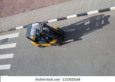 Forklift truck moving on the asphalt road near the pedestrian crossing.