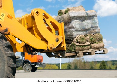Forklift truck transportation pallet with rolled green grass cargo outdoor