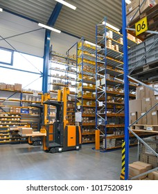 forklift truck in a warehouse of a commercial enterprise, high racks with products for assembly and shipping