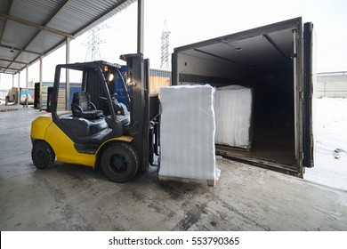 Forklift in warehouse loading dig box into a car outdoors